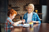 Mindful elderly woman painting with little grandson - 172373648