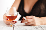 Woman in lingerie sitting at a table and drinking alcohol - 172377602
