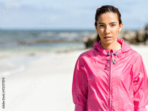 Wall mural Athletic woman in sportswear standing at the seaside