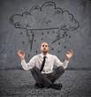Businessman practice yoga under a rainy cloud
