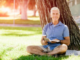 Senior man sittingin park while reading book - 172382803