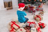 Cute boy in santa hat unwrapping christmas presents - 172392627