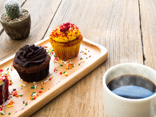 Poster Yellow and chocolate cupcakes put on a spherical wooden plate. Beside of cupcake have Cactus and white coffee mug.All of it rests on wooden table.