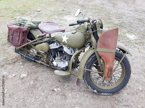 Foto op Plexiglas Fiets military motorcycle with a leather rifle holster attached to a front wheel. The vehicle is painted khaki or war color.