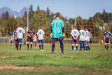 Young soccer goalkeeper and players getting ready for a penalty kick