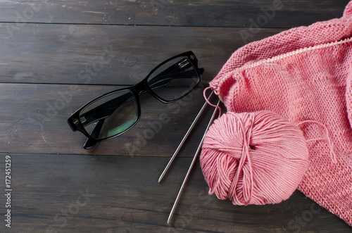 knitting threads and glasses  on a wooden table. Poster