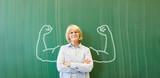 Starke Frau als Lehrer vor Tafel mit Muskeln - 172471076