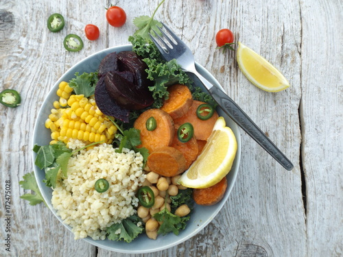 Foto op Canvas Boeddha Vegetarian bowl of buddha. The concept of a vegetarian healthy food. Kale cabbage, bulgur, chickpeas, corn, baked sweet potato and beetroot.
