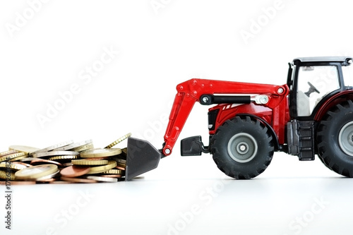 Agricultural tractor toy pushing pile of money suggesting bank savings or deposi