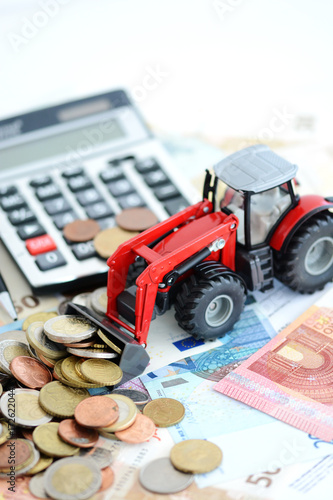 Red agricultural tractor, cash money and calculator suggesting professional financial support - 172622044