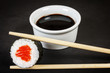 Sushi roll with chopsticks and soy sauce