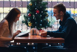 Young couple sitting in cafe in Christmas time reading menu - 172640638