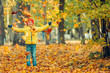 Smiling boy throws leaves in autumn park