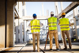 Team of construction engineers working on building site - 172652037
