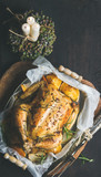 Christmas holiday table set with oven roasted whole chicken stuffed with oranges, bulgur and rosemary, decorative candles over dark wooden background. Top view, copy space, Slow food concept - 172655805