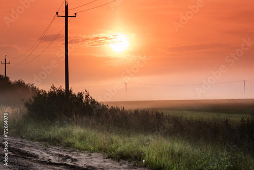 Staande foto Oranje eclat Foggy Landscape.Early Morning Mist. and silhouettes of electricity poles with wires