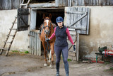 Horserider is walking with horse outdoors in autumn - 172669849