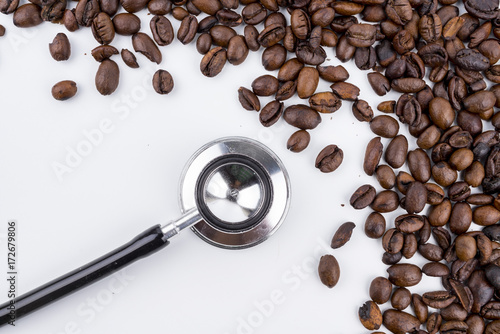 Fotobehang Koffiebonen Concept roasted coffee beans, hot coffee and stethoscope isolated white background
