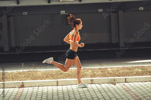 Female runner jogging on the city street under the overpass.City environment.