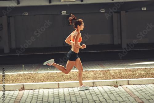 Fotobehang Hardlopen Female runner jogging on the city street under the overpass.City environment.