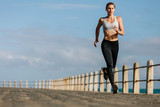 Sportswoman running on a road by the sea - 172686222