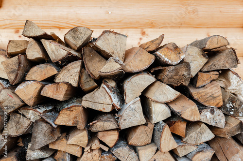 Foto op Plexiglas Brandhout textuur Firewood stacked in a woodpile on wooden background. Background of firewood stack.