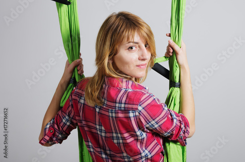 Obraz na płótnie Girl performs exercises with a hammock for yoga / Photo taken in Russia, in the city of Orenburg in the fitness club