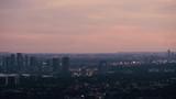 Tight Pan of Distant Metropolis Under Vibrant Pink and Orange Twilight Sky - 172716862