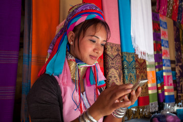 woman wearing the traditional with mobile phone at a weaving in village