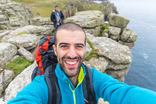 Man hiking and taking a selfie on top of cliffs Poster