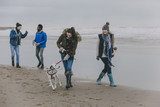 Friends Walking Dog On A Winter Beach