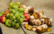 autumn still life of grapes, apples and mushrooms on rough fabric