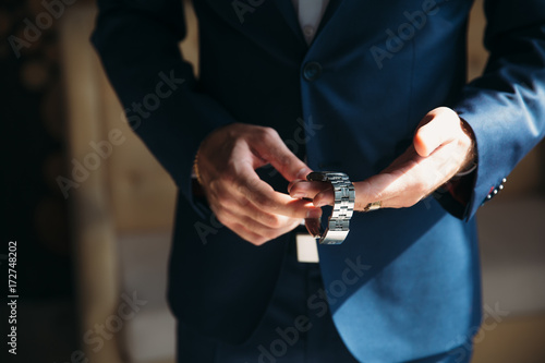 Man in blue jacket with boutonniere wear wrist watches Poster