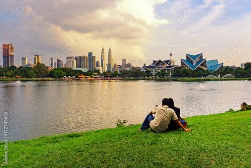 Plagát Unidentified couple at Taman Tasik Titiwangsa during sunset with Kuala Lumpur skyline, Kuala Lumpur, Malaysia