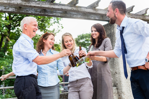 Office colleagues drinking beer after work on terrace celebrating