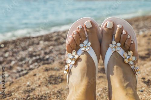 Fotobehang Pedicure красивые женские ноги в пляжной обуви на фоне моря