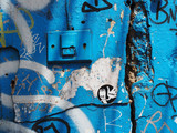 Blue painted old peeled cracked grainy grungy texture concrete wall with bell ring alarm switch panel, and messy graffiti spraying