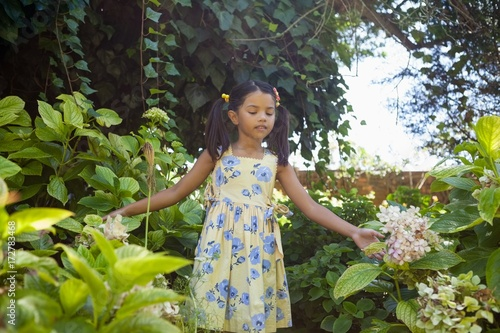 Girl standing amidst green plants