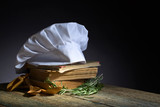 Old culinary books , chef hat and wooden spoons . - 172785413