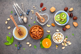 Ingredients for a healthy foods background, nuts, honey, berries, fruits, blueberry, orange, almonds, walnuts and chia seeds .The concept of healthy food set up on dark stone background. Flat lay . - 172793013