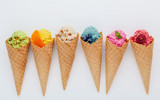 Various of ice cream flavor in cones blueberry ,strawberry ,pistachio ,almond ,orange and cherry setup on white wooden background . Summer and Sweet menu concept. - 172793221