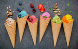Various of ice cream flavor in cones blueberry ,strawberry ,pistachio ,almond ,orange and cherry setup on dark stone background . Summer and Sweet menu concept. - 172793674