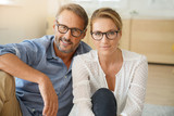 Mature couple with eyeglasses sitting on carpet at home - 172793871