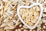 Oat groat in heart-shaped bowl, grain on oatmeal ears plants background - 172794627
