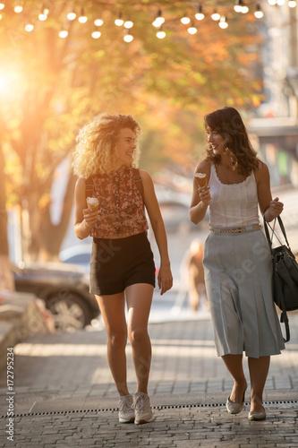 Sticker Happy women friends walking in city street eat ice cream