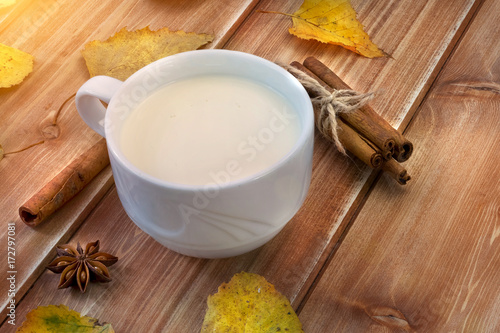 Milk in the white cup, cinnamon stick and autumn yellow leaves on wooden table
