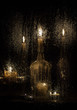 Candles and bottles behind a wet glass on a dark background.
