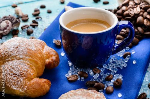 Poster Koffiebonen Caffè e brioche in blu, fuoco selettivo