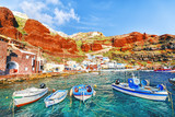 Old port in Oia - Ia village on Santorini volcano island in Cyclades archipelago in Greece, European country. Fishing boats at foreground, ginger rocks in background. Santorini is popular resort. - 172812812