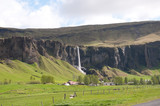 Waterfall and small farm in remote Iceland